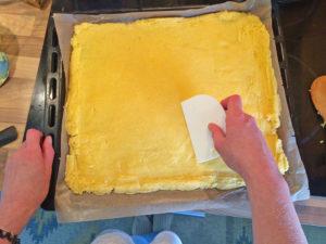 Polenta-Pizza Teig ausbreiten mit dem Teigspachtel